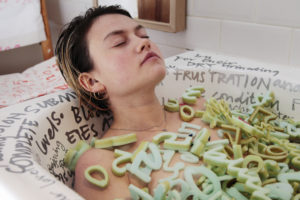 A woman lies naked in the bath, eyes closed and hair slicked back away from her face. Her body is covered with foam numbers and letters, and written on the bath are words and phrases from articles related to Type 1 Diabetes