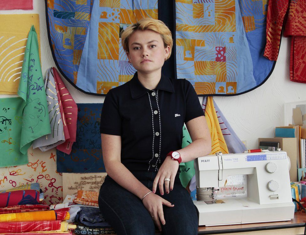 A woman with short dyed blonde hair, posing in her art studio among printed textiles and a sewing machine.